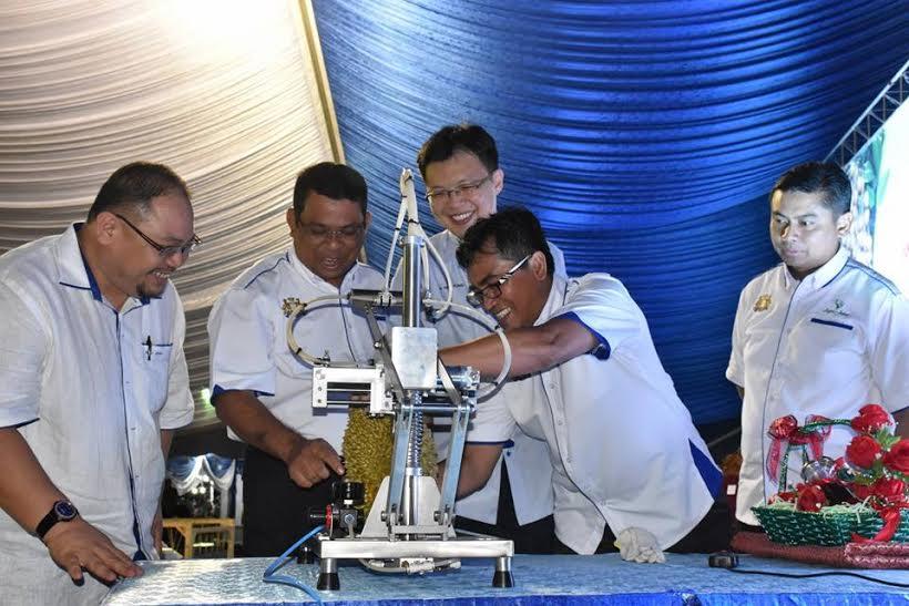 Ayub (dua,kiri) mencuba mesin membuka durian selepas merasmikan Mini Agro Johor peringkat daerah Segamat