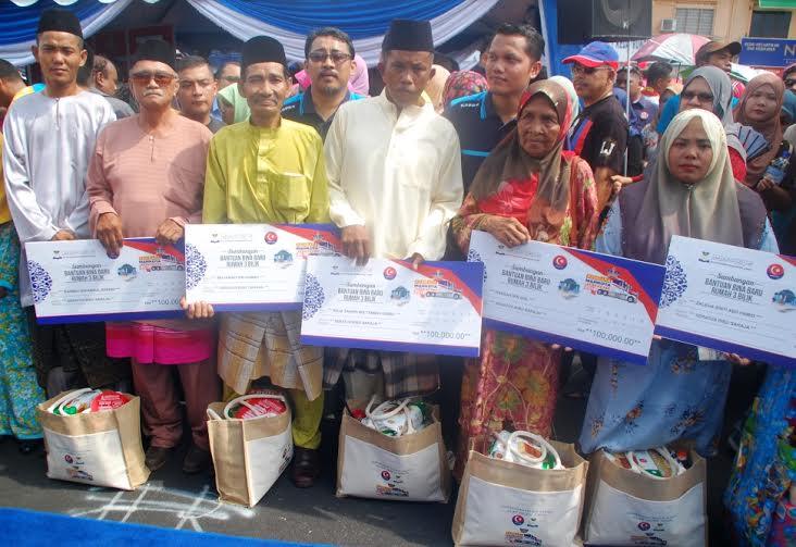 Lima mangsa banjir di Kampung Seberang Batu Badak menunjukkan replika Sumbangan Bantuan Bina Baru Rumah sewaktu Kembara Mahkota Johor (KMJ) baru-baru ini.