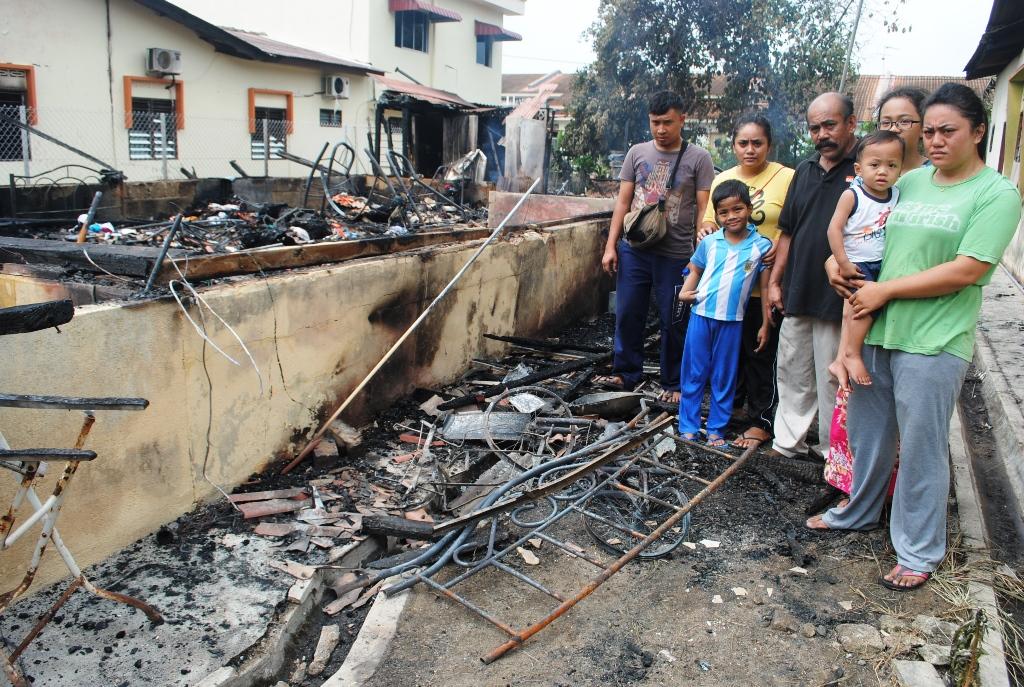 Hashim (tengah) melihat keadaan rumahnya yang hangus bersama anak, menantu dan cucunya